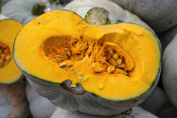 halved lumina pumpkin with grey skin and orange fruit flesh, decorative autumn vegetable for halloween and thanksgiving, selected focus