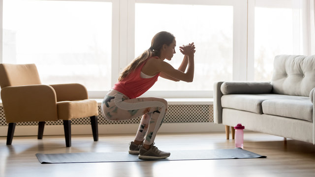 Sporty young woman doing squat morning exercise in living room