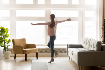 Happy active young woman dancing alone in modern living room