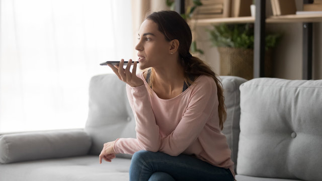 Young woman holding phone using mobile voice recognition at home