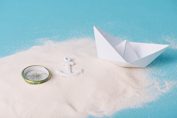 sand with paper boat, compass and anchor on blue background