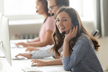 Call center employee female sitting at workplace pose for camera