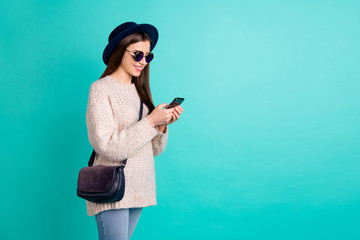 Fototapete - Portrait of cute inspired lovely girl use her smart phone comment post wear white knitted jumper denim jeans isolated over teal color background