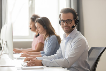 Smiling call center worker sitting at workplace looking at camera
