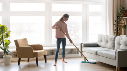 Young woman housewife clean floor in modern living room
