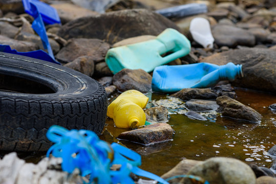 Earth plastics pollution global enviroment emergency. Old car tire in dirty water stream with plastic bottles and trash.