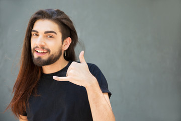 Cheerful long haired guy showing call me gesture. Handsome bearded young man standing over grey background, making phone with hand. Telephone concept