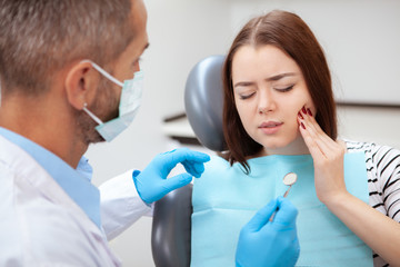 Young woman having toothache, sitting in a dental chair at the clinic. Female patient with terrible toothache visiting dentist