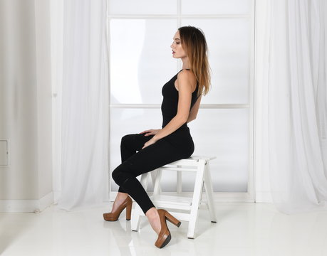 young woman sitting on a chair in sexy pose, side view