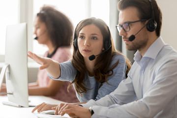 Call center female worker helping to man new employee colleague