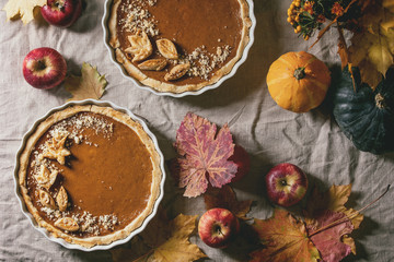 Traditional homemade autumn pumpkin pies for Thanksgiving or Halloween dinner served in ceramic...
