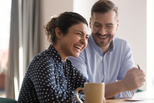 Happy young indian business woman laughing with male colleague in office