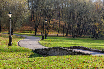 Paved sidewalk and small old stone bridge in the landscape Tsaritsyno park in Moscow, Russia
