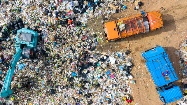 Garbage trucks unload garbage to open landfill, Surface and subsurface water contamination, modern hydraulic. Aerial top view garbage pile