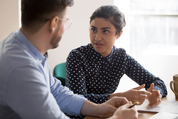 Indian female mentor worker talking to male coworker in office