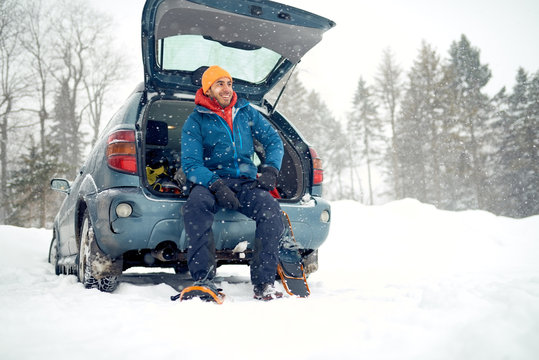 Solo indian man traveller camping through an evergreen winter forest in Canada
