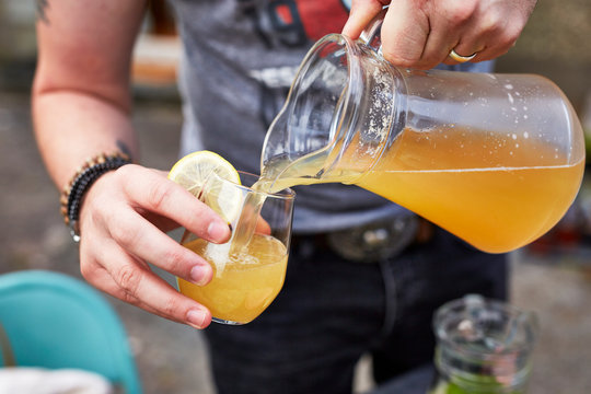 Ginger and coriander seed shandy being poured from a jug into a glass