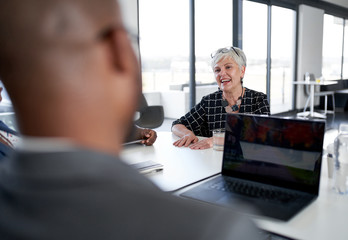 Candid shot of elegant mature female boss laughing with diverse multi-ethnic professional colleagues in meeting
