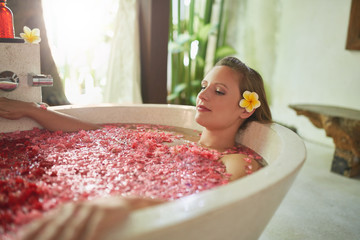 Beautiful millennial woman with tropical flower accessory sitting in large bathtub filled with flower petals in luxurious spa setting