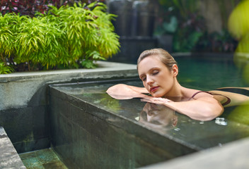 Healthy woman relaxing outdoors in sunny and plant surrounded swimming pool of luxurious resort...