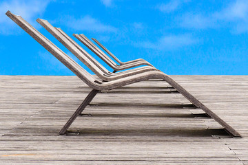 wooden deck chairs on a large beach of wooden planks under azure blue sky