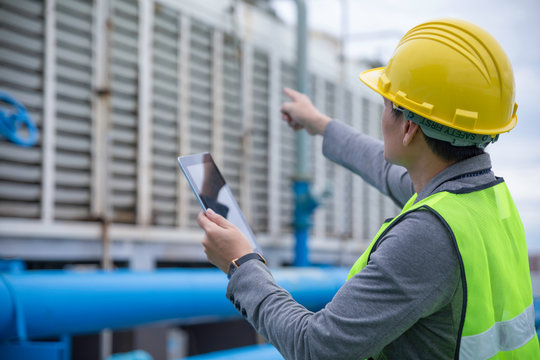 Engineer with safety helmet at the construction site typing on a digital tablet