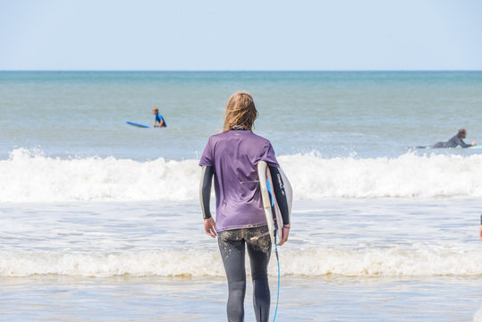 young blonde surf chick wearing a wetsuit walking with her soft top surfboard towards the blue ocean. Beautiful summer day on a French beach.