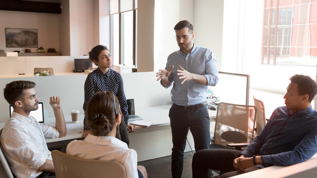 Serious team leader talk to diverse business people at meeting