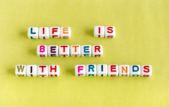"Quote ""Life is better with friends"" made out of colorful beads on yellow background"