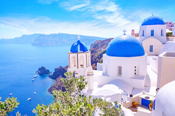 Fotobehang Santorini Beautiful Oia town on Santorini island, Greece. Traditional white architecture and greek orthodox churches with blue domes over the Caldera, Aegean sea. Scenic travel background.