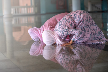 Hands of two muslim woman on the reflection floor praying in traditional clothes.