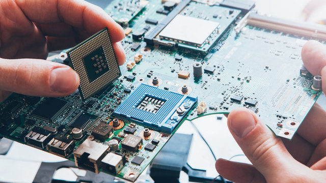 Tech support. Hardware repair. Engineer installing CPU on motherboard.