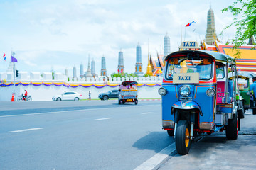 asia local travel in city activity with local taxi (tuk tuk) parking for wait tourism on street of bangkok Thailand with grand palace landmark background