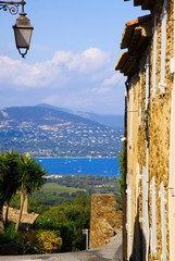 View beyond ancient house wall and street lamp from mediterranean hill top village Gassin on blue sea of gulf of St. Tropez. Blurred mountain with city of St. Maxime background.