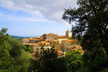 Panoramic view beyond trees on French mediterranean medieval village with church tower on hill top - Ramatuelle, Cote d´Azur, France