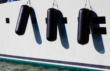 View on white boat side of luxury yacht with three black fenders in natural bright sun light - Marine de Cogolin, France