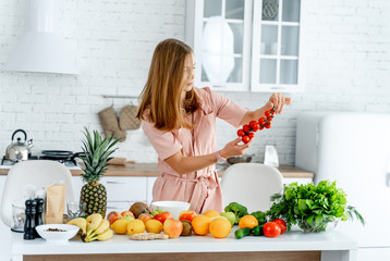 Woman in kitchen ready to prepare meal with vegetables and fruits. Woman is looking at tomatoes in her hands. Kitchen background. Healthy food. Vegans. Vegeterian.
