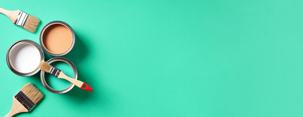 Paint brushes and open paint cans with on trendy green background. Top view, copy space. Appartment...