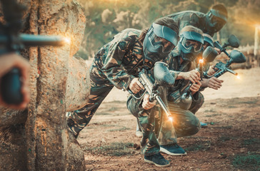 Paintball players aiming with gun