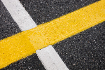 yellow and white lines on the road, asphalt marks on the street