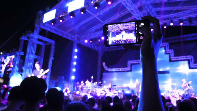 People live with mobile phone at a festival concert with crowd people raised hands and attending a concert. Blue black light by stage lights. Summer music festival concept.