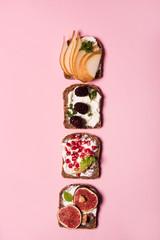 Trendy sandwiches with fresh fruits, like pomegranate, figs, mulberry and pears. Healthy food concept with different sandwiches with vibrant color style.