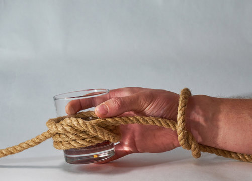 A man's hand holds a glass of whiskey tied in a knot with a jute rope. Alcohol addiction