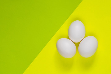 three chicken eggs lie on a yellow-green background