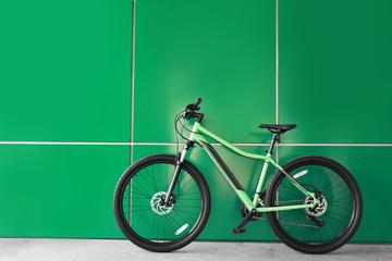 Fototapeten Fahrrad New modern color bicycle near green wall outdoors