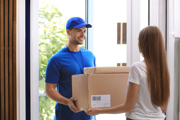 Woman receiving parcels from courier on doorstep