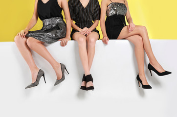Women wearing stylish shoes on color background, closeup