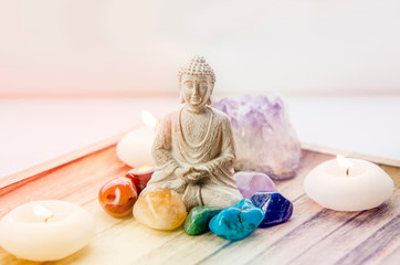 All seven chakra colors crystals stones around sitting Buddha figurine on natural wooden tray. Balance and calm energy flow in home concept.