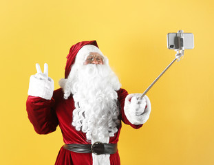 Authentic Santa Claus taking selfie on yellow background