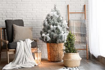Stylish interior with beautiful Christmas tree near white brick wall